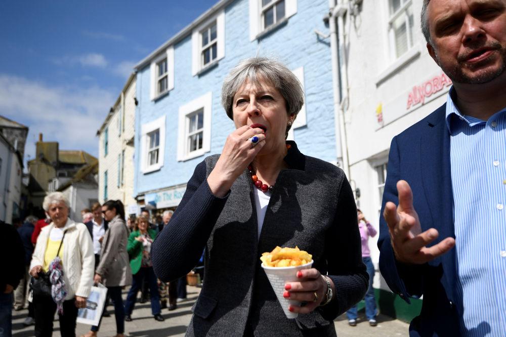 英國首相特蕾莎·梅與英國梅沃吉西市市民見面時吃薯片。