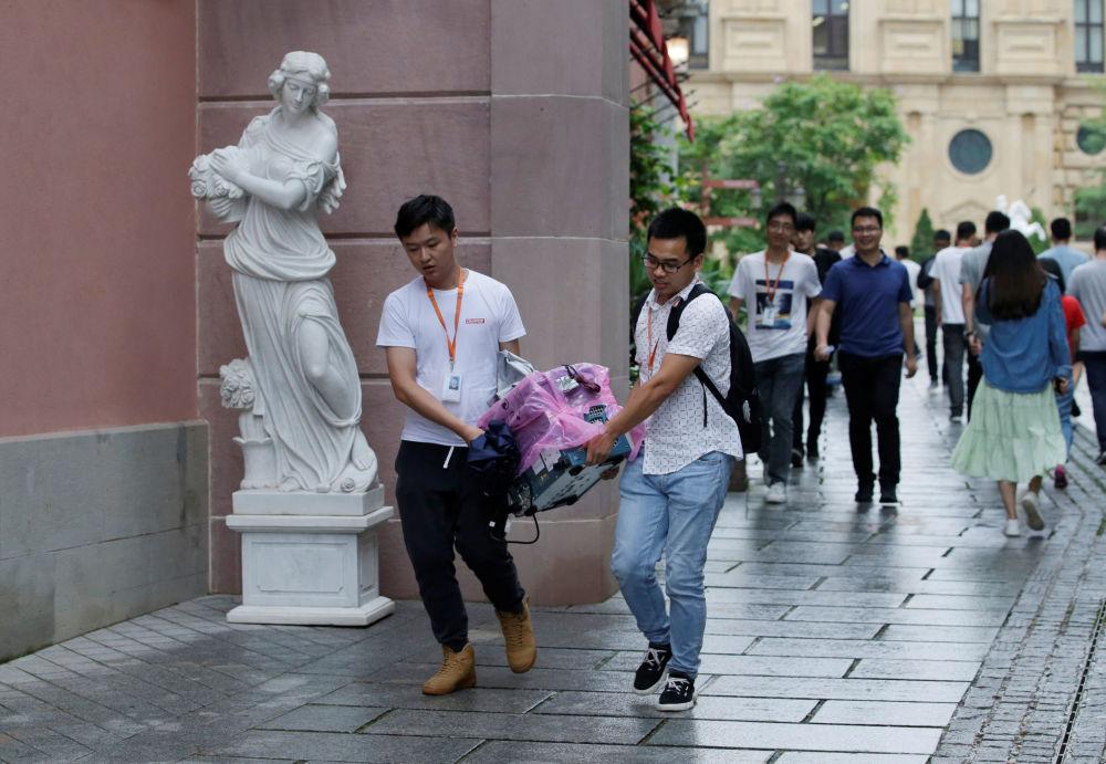 華為公司員工拿著設備路過雕像,中國東莞。為公司研發人員而設的「牛角」園區按歐洲風格建造