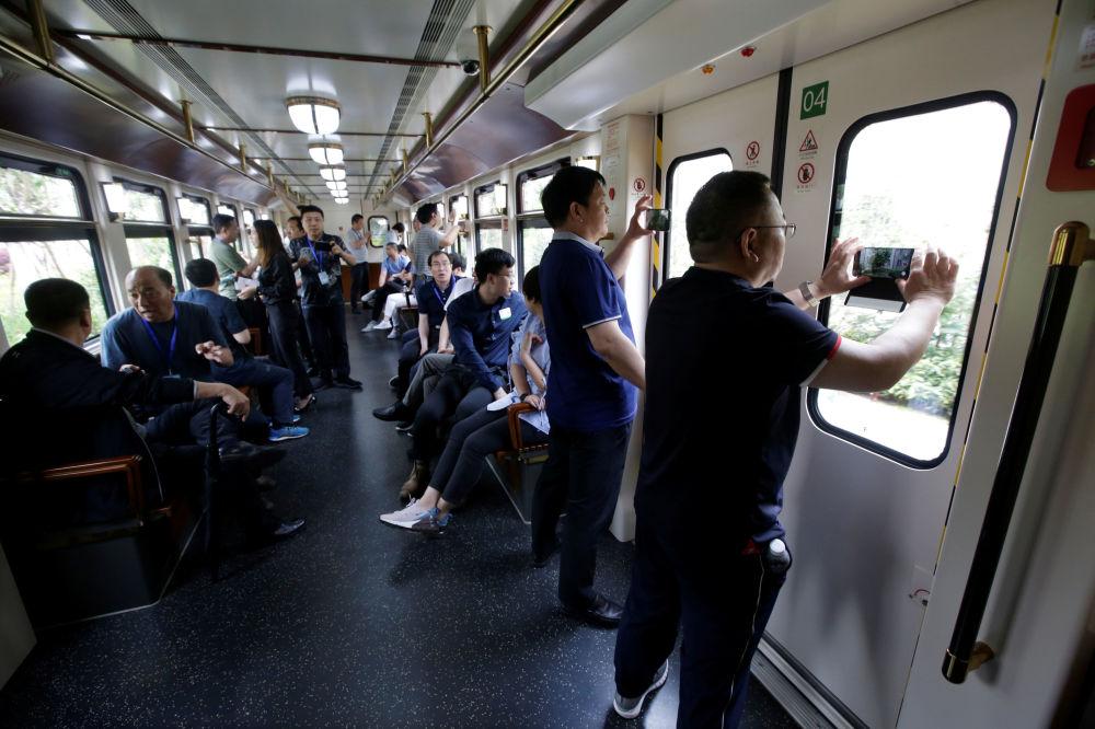 華為公司辦公室的訪客在電氣火車上拍攝。中國東莞。從「牛角」園區有電車和火車通往包括深圳總部在內的公司其他園區和中心