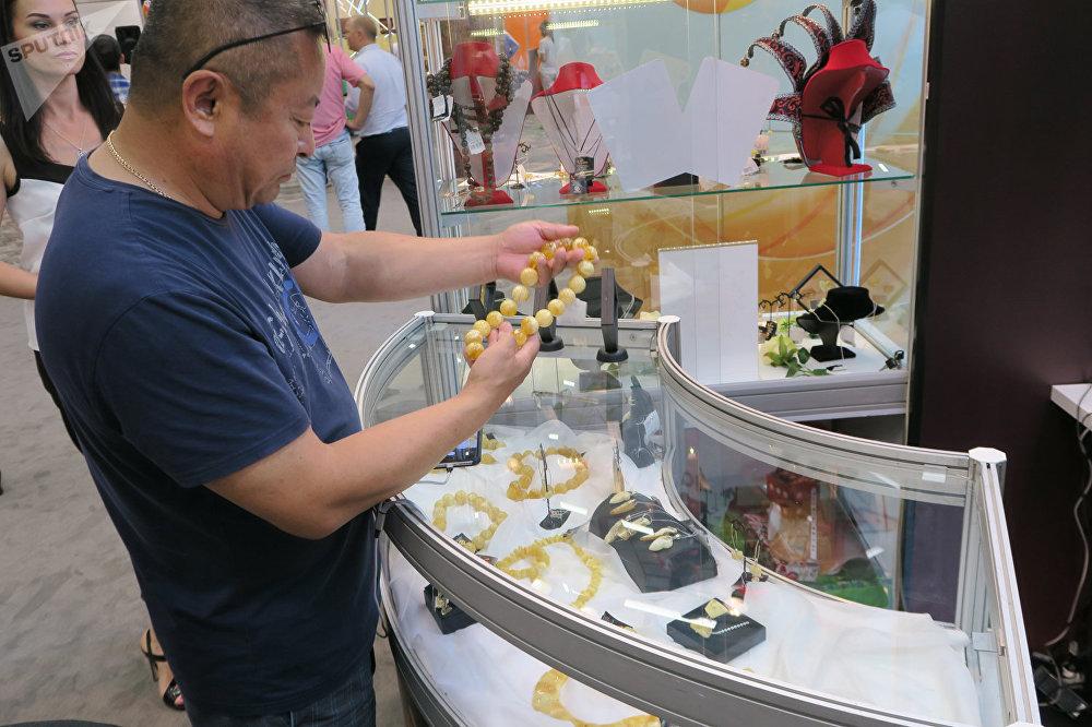 參觀展會的中國人在選擇白蜜蠟珠子做成的項鍊。其價格超過了3萬元。