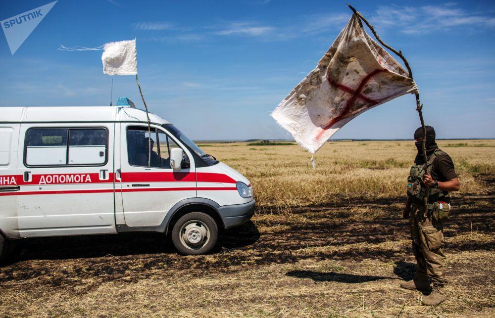 一名烏克蘭軍人打著白旗在中立區轉交死者屍體。