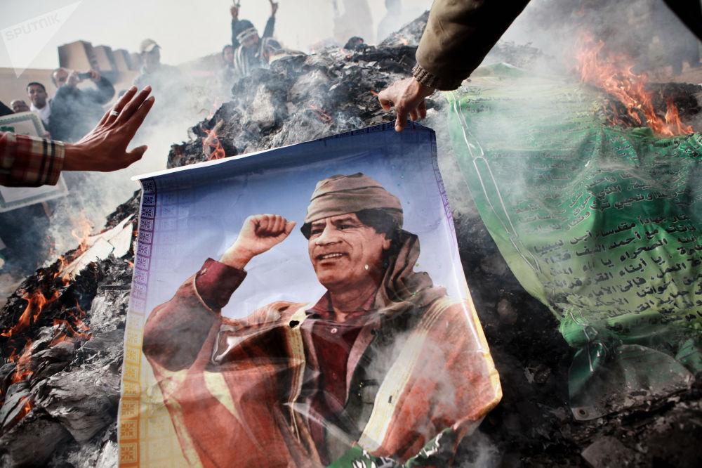 班加西居民焚燒卡扎菲肖像、卡扎菲名言標語和卡扎菲的《綠皮書》。