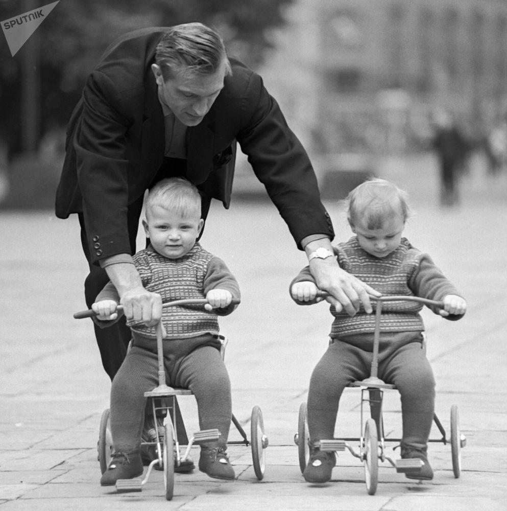 一名父親在教雙胞胎寶寶騎三輪自行車。1968年。