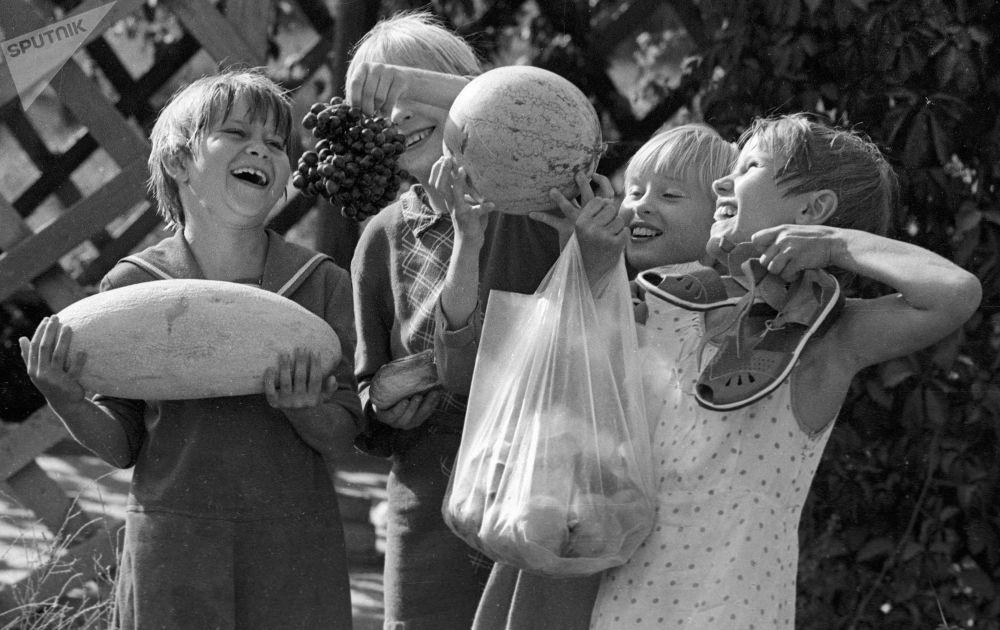 塔什乾一家孤兒院中手提懷抱香瓜、西瓜、葡萄和桃的學生們,這些都是在孤兒院院子里種植的水果。1983年。
