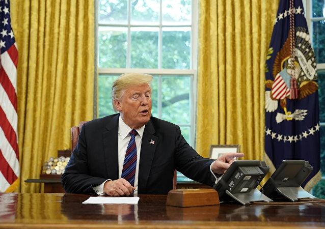 US President Donald Trump looks at his telephone from the Oval Office at the White House on August 27, 2018 in Washington,DC.
