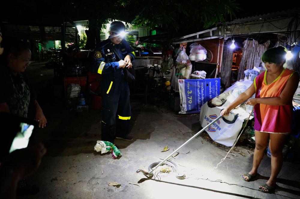 一名泰國女子在救援隊趕來前手持棍子按住在自家捕到的眼鏡蛇。