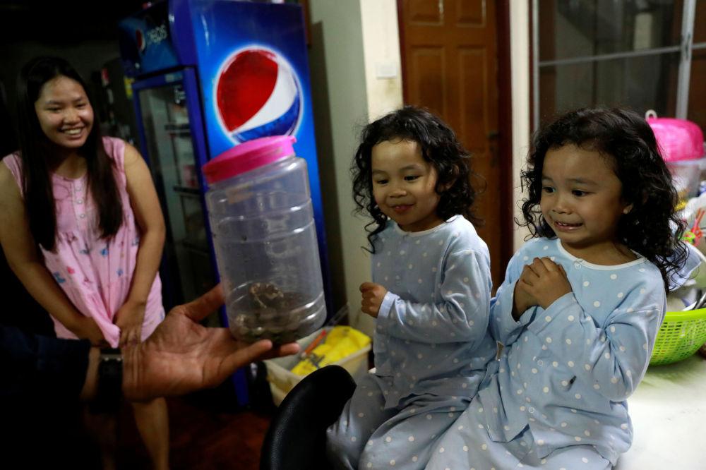 曼谷一些小女孩在看自己家中抓到的蛇。