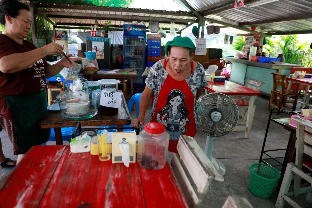泰國曼谷街頭的商販在看被抓的放到塑料瓶中的眼鏡蛇。