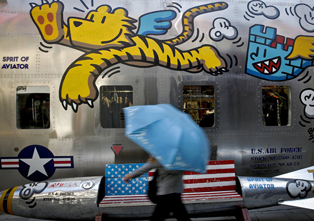A woman walks by a bench painted with an American flag outside a fashion boutique selling U.S. brand clothing at the capital city's popular shopping mall in Beijing