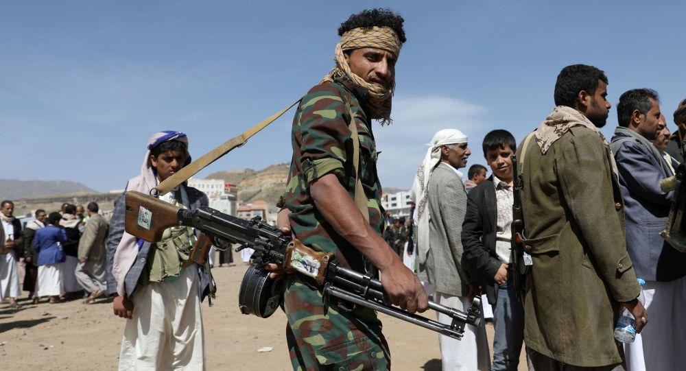 Сторонник хуситов с оружием стоит в очереди за продовольствием