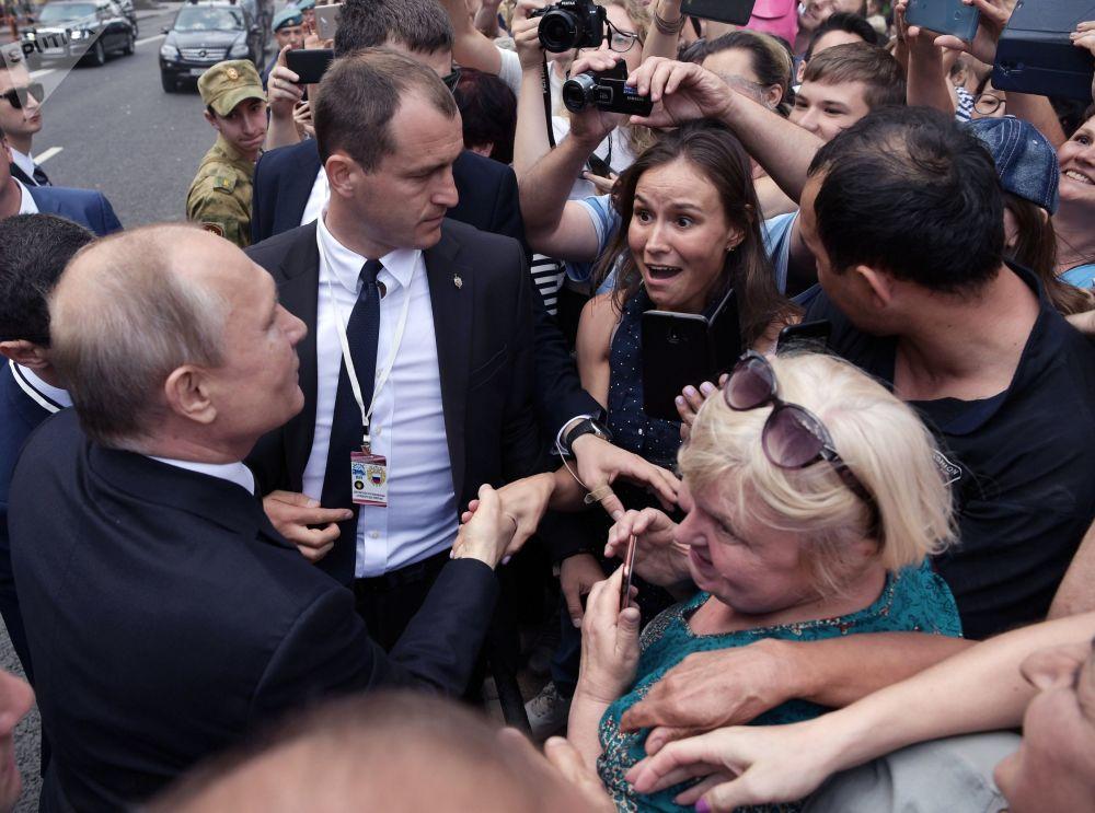 2019年7月28日,在聖彼得堡舉行的俄羅斯海軍節海上閱兵式結束後,俄羅斯總統,最高統帥弗拉基米爾·普京沿金鐘堤散步時與市民們交流。
