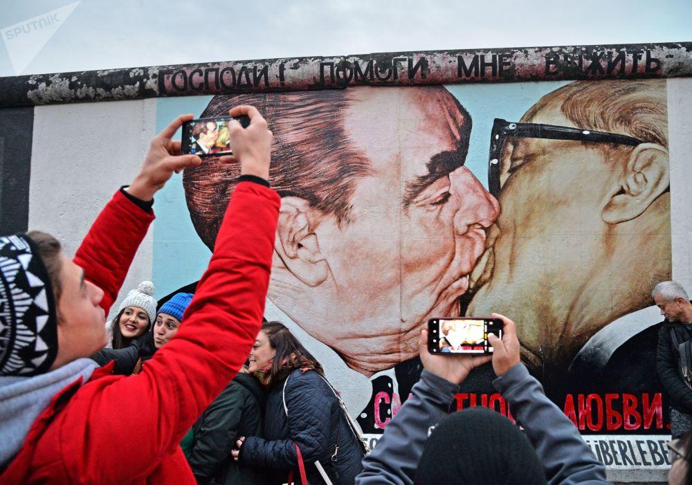 人們在磨坊街(Mühlenstrasse)柏林牆藝術作品展示區Dmitri Wrubel繪制的《我的上帝,助我在這致命之愛中存活》或稱《兄弟之吻》的畫作旁