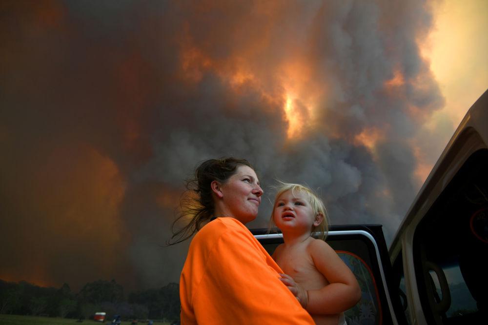 澳大利亞自然火災的煙霧中抱著孩子的女子。