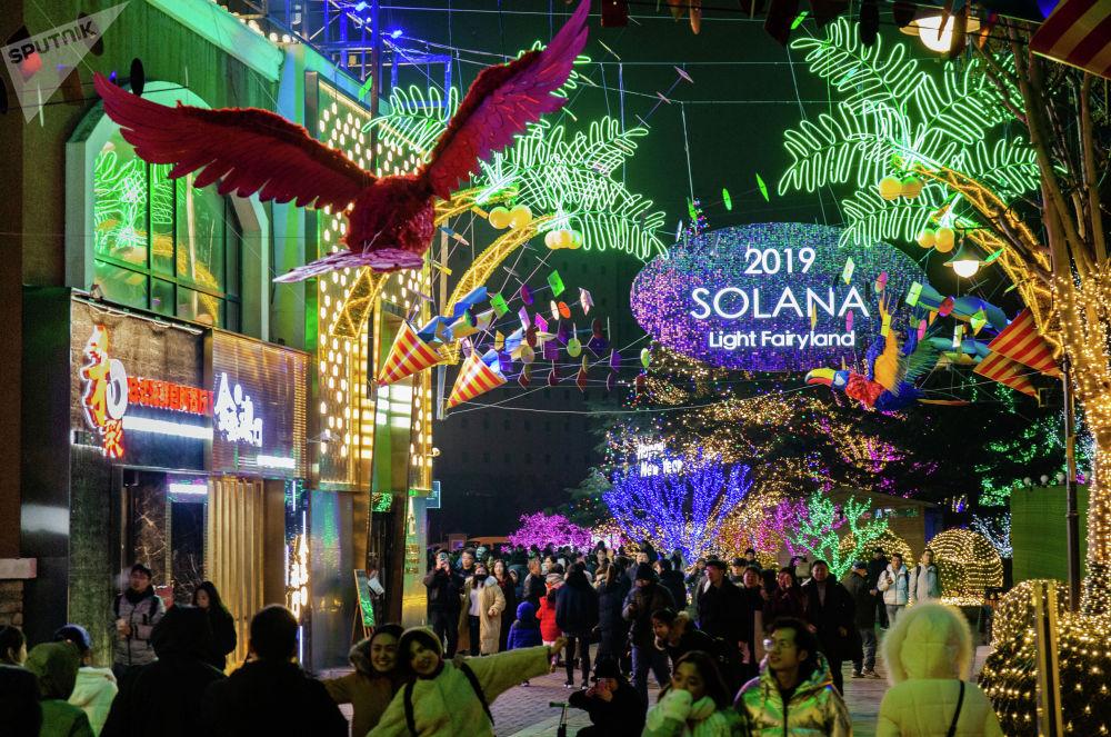 年輕人以北京藍色港灣的節日燈光為背景拍照