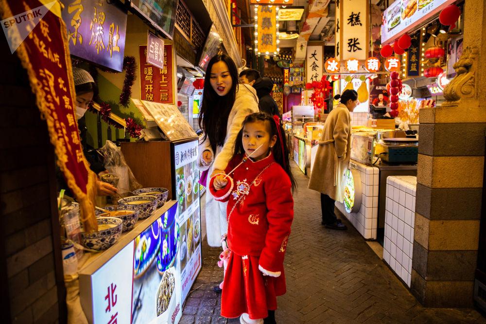 大人帶著孩子在假期前來前門大街品嘗傳統糕點