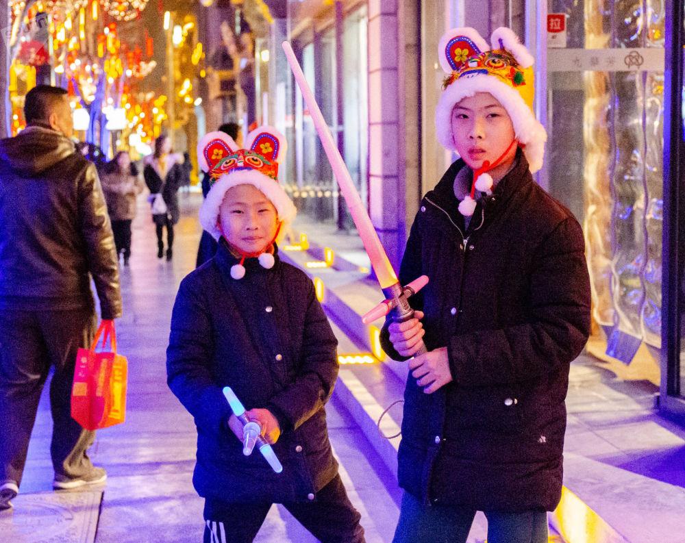 戴著新年帽子的兄弟倆在玩耍寶劍