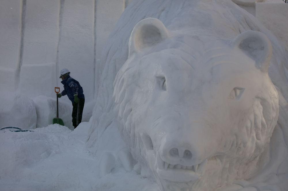 日本札幌冰雪節一名工作人員拿著雪橇站在雪雕邊