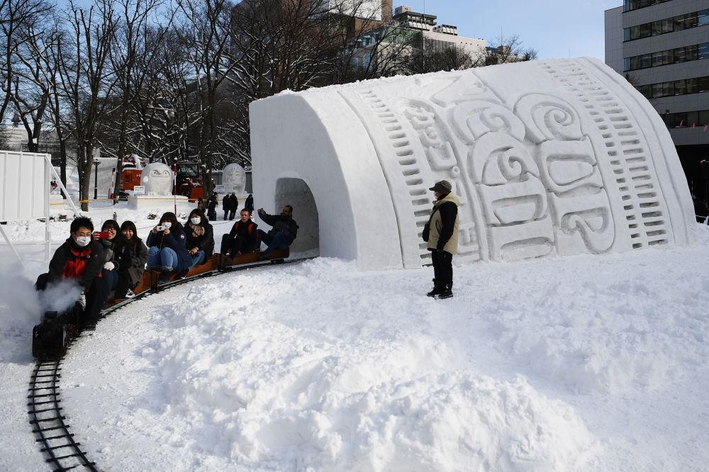 遊客穿行在日本札幌冰雪節的雪雕之間
