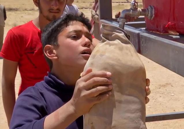 敘利亞軍營里的一名小男孩在舀水